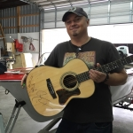 """Edwin McCain in his """"Boats Have Souls"""" shop, with both Auction Guitar and Boat"""